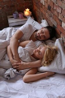 Casal deitado na cama de pijama duplo e dormindo