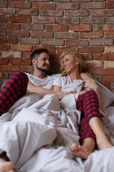 Casal deitado na cama de pijama duplo e rindo