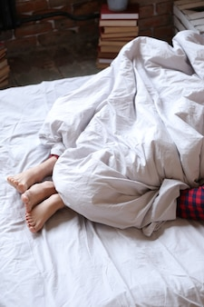 Casal deitado na cama de pijama duplo, vista de pés