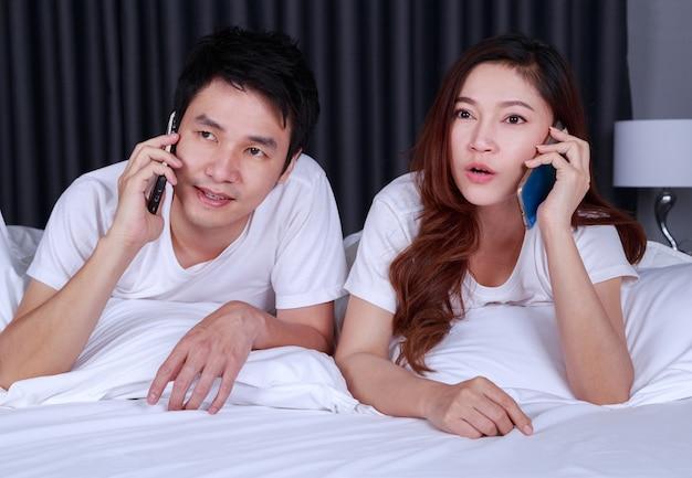 Casal deitado na cama e falando no celular