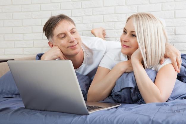 Casal deitado na cama usando laptop se comunicando on-line em casa, homem e mulher digitando no computador, desfrutando de compras na internet ou conversando em redes sociais no quarto.