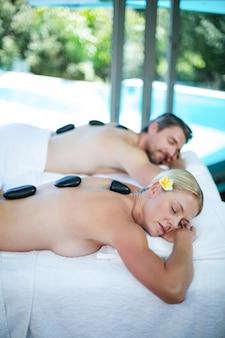 Casal deitado na mesa de massagem