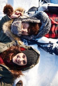 Casal deitado na neve branca