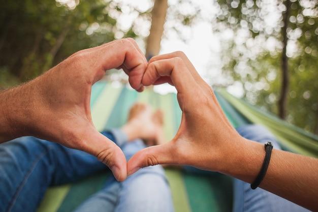 Casal deitado na rede fazendo o símbolo do coração