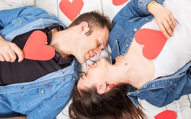 Casal deitado no chão de madeira com corações