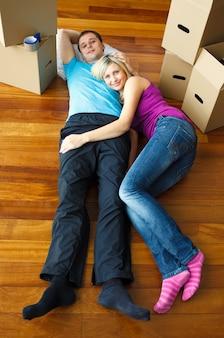 Casal deitado no chão. mudança de casa