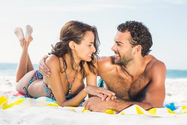 Casal deitado sobre uma toalha na praia