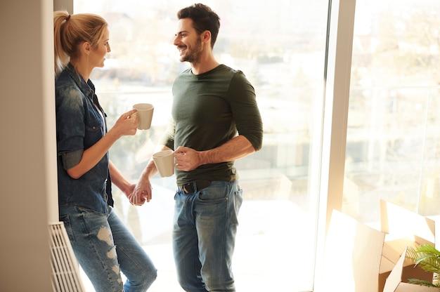 Casal dentro da nova casa durante a pausa para o café