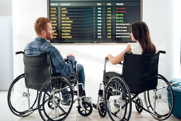 Casal desabilitado no saguão do aeroporto.