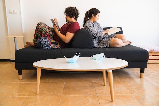 Casal descansa em um sofá lendo e usando um tablet como bloco de notas enquanto suas máscaras cirúrgicas repousam na mesa da sala