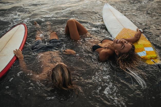 Casal descansando na água com pranchas de surf