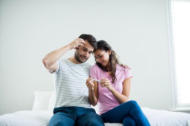 Casal descobrindo resultados de um teste de gravidez no quarto de casa