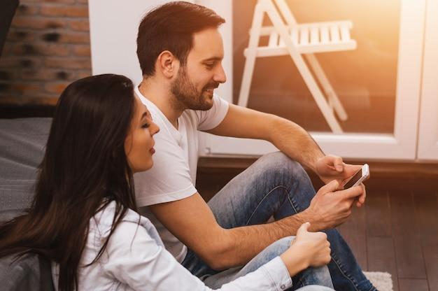 Casal descontraído ou amigos usando um smartphone juntos, sentados no chão na sala de estar em casa