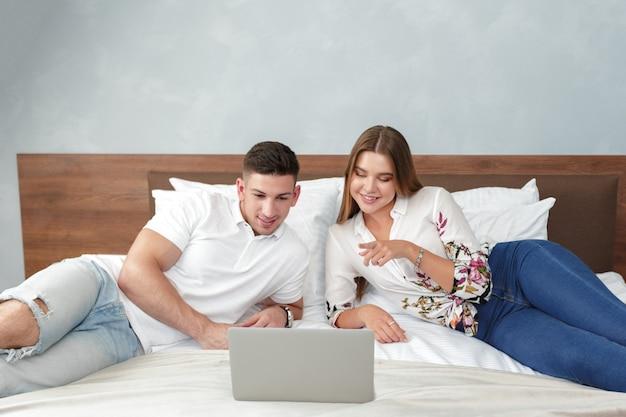 Casal descontraído, trabalhando na cama