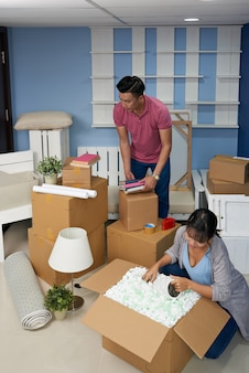 Casal desembalar caixas em casa