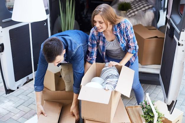 Casal desembalar caixas para morar