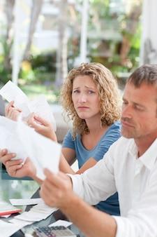 Casal desesperado, calculando suas contas domésticas