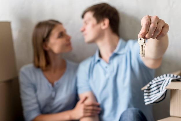 Casal desfocado segurando as chaves de uma antiga propriedade antes de se mudar