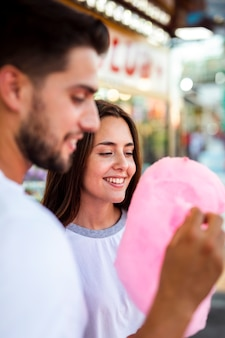 Casal desfrutando de algodão doce rosa