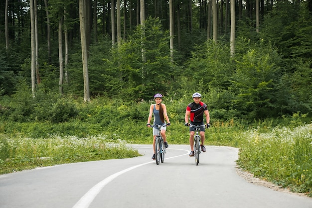 Casal desportivo, andar de bicicleta de montanha na estrada da floresta