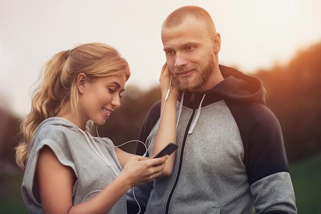 Casal desportivo caucasiano namoro após o treino, ouvindo música, se divertindo juntos. esportes e atividades ao ar livre, conceito de tecnologia e relações pessoas