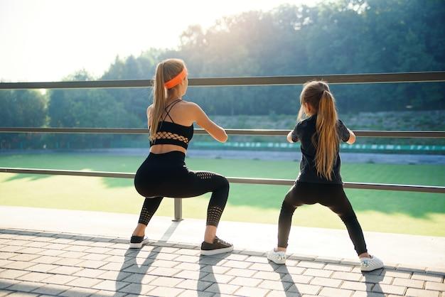 Casal desportivo fazendo exercício de salto durante treino de fitness no estádio ao ar livre
