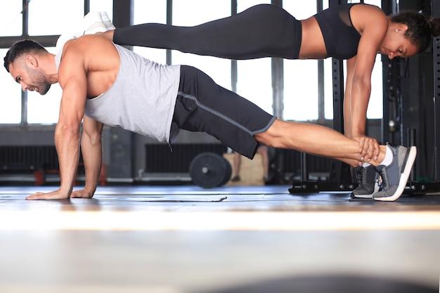 Casal desportivo fazendo exercícios de prancha no ginásio.