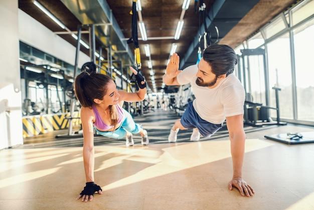 Casal desportivo fazendo flexões e dando mais cinco. interior do ginásio.