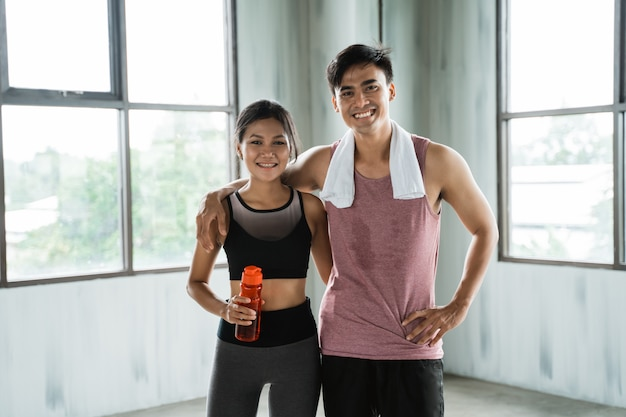 Casal desportivo mãos na cintura na sala de ginástica