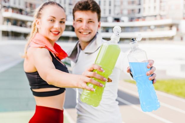 Casal desportivo mostrando bebidas energéticas