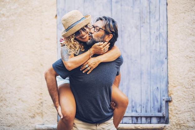 Casal despreocupado, gastando tempo de lazer juntos ao ar livre, homem dando carona a alegre mulher tatuada em óculos escuros e chapéu de palha. homem amoroso beijando a esposa enquanto a carrega nas costas.