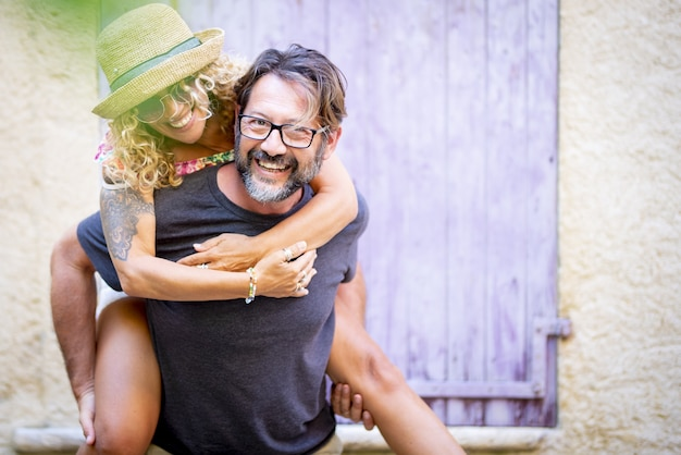 Casal despreocupado, gastando tempo de lazer juntos ao ar livre, homem dando carona a alegre mulher tatuada em óculos escuros e chapéu de palha. mulher curtindo carona nas costas do marido
