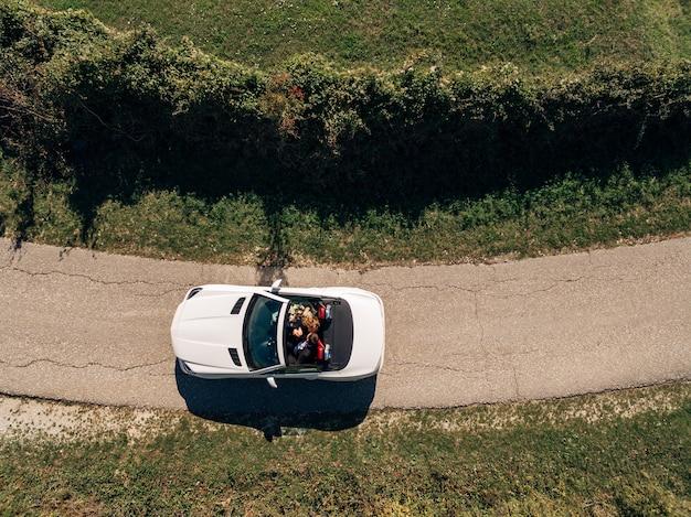 Casal dirige um carro branco na estrada