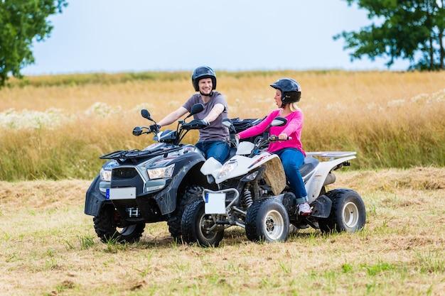 Casal dirigindo off-road com moto-quatro ou atv