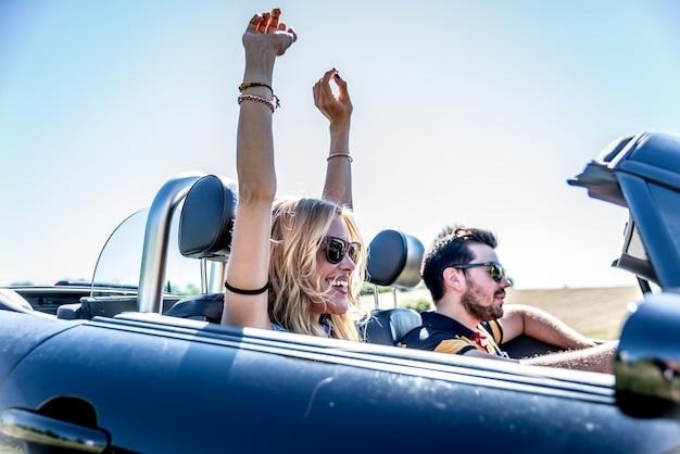Casal dirigindo um carro conversível e se divertindo