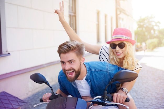 Casal dirigindo uma scooter na cidade