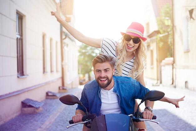 Casal dirigindo uma scooter pela cidade