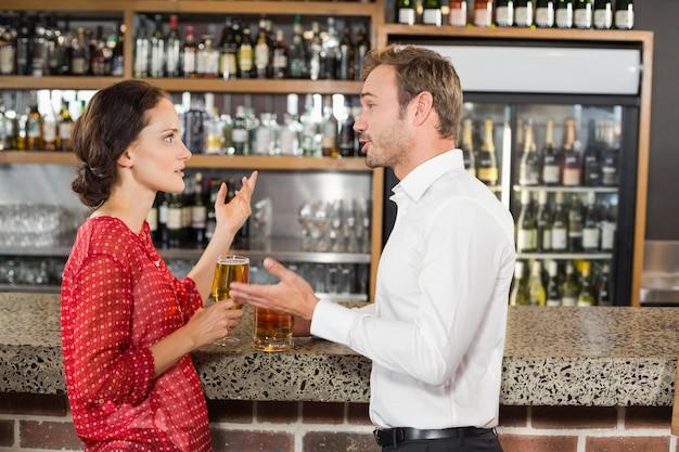 Casal discutindo e segurando cerveja
