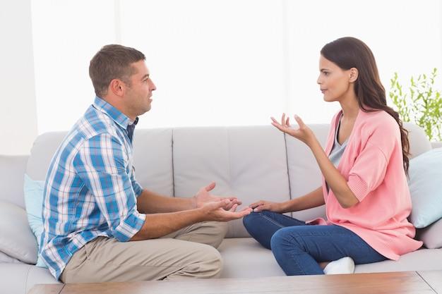 Casal discutindo enquanto está sentado no sofá