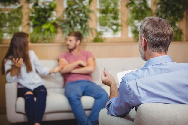 Casal discutindo na sessão de aconselhamento com um médico