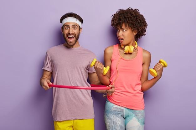 Casal diversificado tem treinamento no ginásio. rapaz sorridente a posar com bambolê