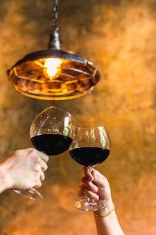 Casal do conceito de celebração tilintando de copos de vinho tinto.
