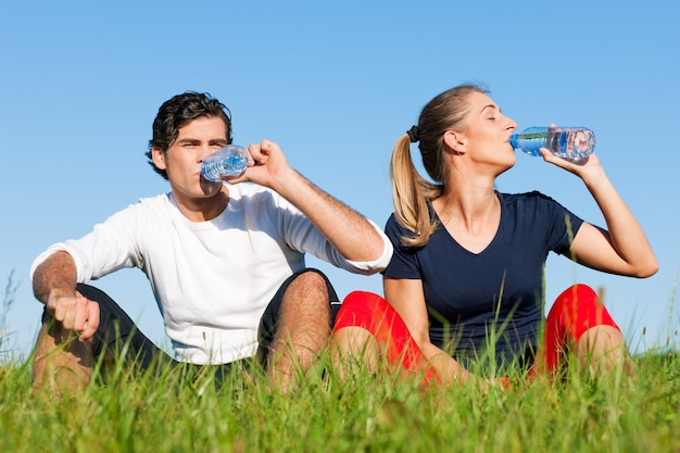 Casal do corredor descansando e bebendo água