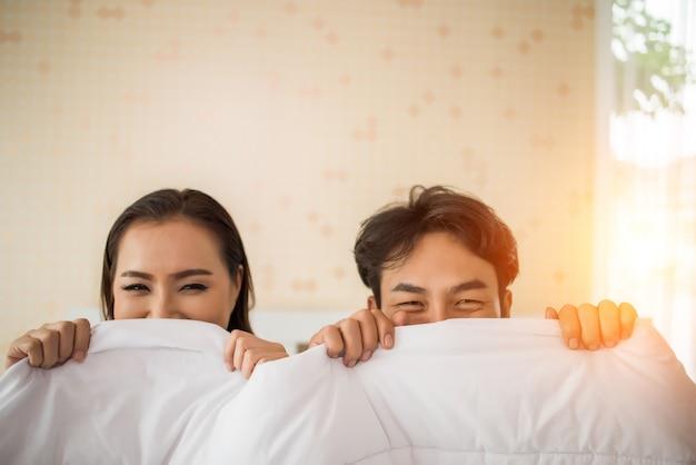 Casal doce brincando debaixo do cobertor na cama