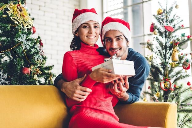 Casal doce romântico em chapéus de papai noel se divertindo decorando a árvore de natal e sorrindo enquanto comemorava a véspera de ano novo e aproveitando o tempo juntos