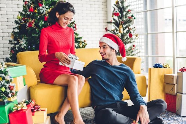 Casal doce romântico em gorros se divertindo decorando a árvore de natal e sorrindo enquanto comemorava a véspera de ano novo e aproveitando o tempo juntos