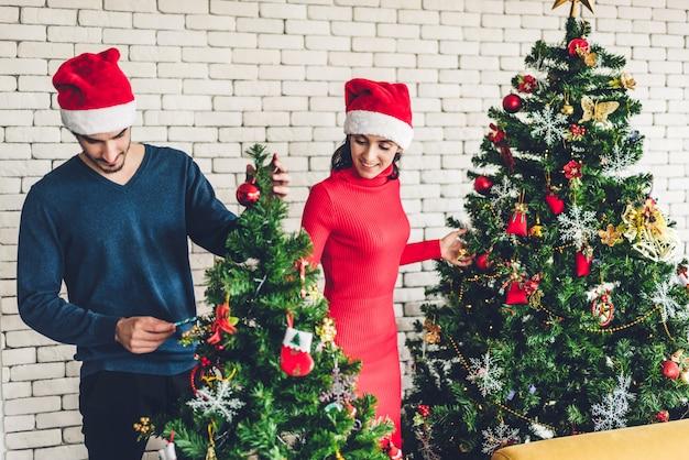 Casal doce romântico em gorros se divertindo decorando a árvore de natal e sorrindo enquanto comemorava a véspera de ano novo