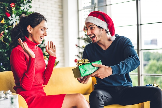 Casal doce romântico em gorros se divertindo decorando a árvore de natal e sorrindo