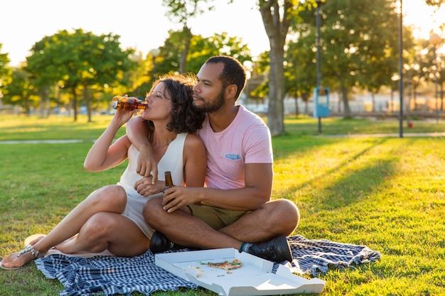 Casal doce tranquilo desfrutando de um jantar no parque