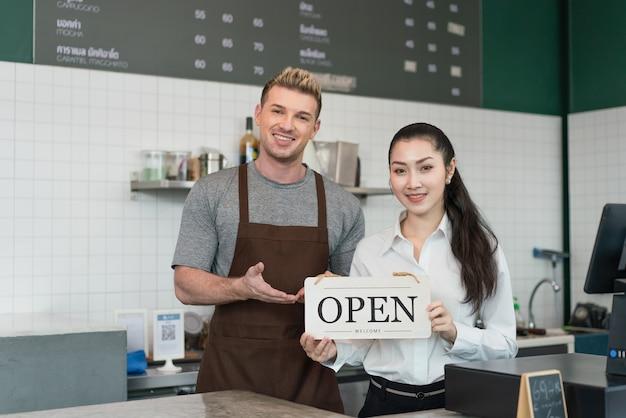 Casal dono de barista sorrindo e segurando uma placa aberta de boas-vindas ao cliente na cafeteria
